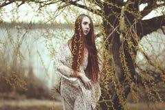 一个浪漫女孩的画象有红色头发的在风在柳树下 免版税库存照片