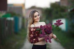 一个浪漫微笑的少妇的画象有丁香户外浅景深花束的  库存图片