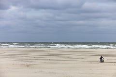 一个海滩的横向与一个人和他的自行车的 库存照片