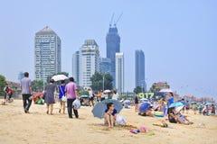 一个海滩的人们与背景的摩天大楼,烟台,中国 库存图片