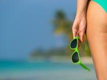 一个海滩的女孩与在手中玻璃在热带islan 免版税库存照片