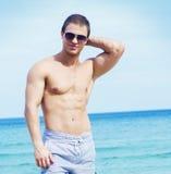 一个海滩的年轻,英俊和运动人在夏天 库存照片