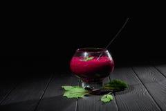 一个深红色的甜菜圆滑的人点心 一块大透明玻璃用在黑背景的厚实的菜鸡尾酒填装了 库存照片