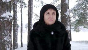 一个深色的女孩在冬天公园站立或森林和神色入距离 照相机安定器在年轻附近移动 股票录像