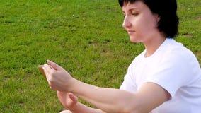 一个深色的女孩坐绿草并且使用智能手机 年轻女人传送在人脉的信息 股票录像