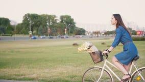 一个深色的女孩的侧视图有骑一辆自行车的长的头发的在有花的城市在篮子,缓慢的mo, steadicam射击 影视素材