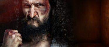 一个深色头发的皮包骨头的战士的特写镜头画象有ey的黑色的 免版税库存照片