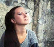 一个混凝土墙的背景的沉思女孩 库存图片