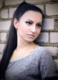 一个混凝土墙的背景的沉思女孩 图库摄影