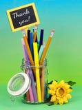一个清楚的密封瓶子充满五颜六色的制造商和铅笔在一毕业的蓝绿色blackground与黄色丝绸花 免版税库存照片