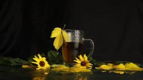 一个清楚的玻璃杯子在热的茶立场以后雨是湿的在秋天风景中间:被染黄的落叶,黄色花 股票录像