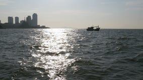 一个渔船的剪影在反对一条晴朗的道路的强光的海 泰国 聚会所 芭达亚 股票录像