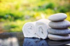一个温泉治疗集合、按摩石头和一块白色特里毛巾在一张优美的花岗岩桌上在庭院里 库存图片