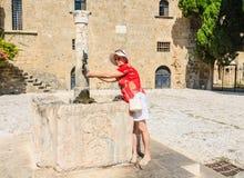 一个游人在水的水源的老镇 罗得斯 希腊 库存照片