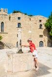 一个游人在水的水源的老镇 罗得斯 希腊 图库摄影