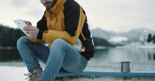 一个游人的画象细节在自然中间的在一座多雪的湖和山旁边,坐一条蓝色小船和 股票视频