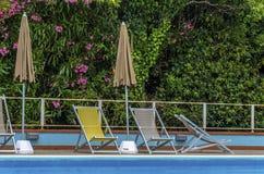 一个游泳池的看法与deckchairs和阳伞的 免版税库存图片