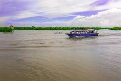 一个游船和一个小河船航行在a下的一条河 免版税库存图片