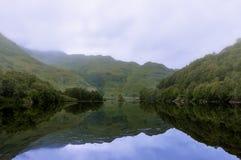 一个湖和山的有薄雾和平静的风景在苏格兰,英国的高地 免版税库存照片