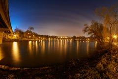 一个湖在一个公园在与光和他们的反射和公寓的晚上 免版税图库摄影