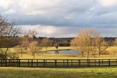一个湖在一个老村庄在英国作为冬天太阳出现af 库存图片
