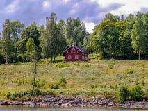 一个湖的典型的红色木屋在瑞典 免版税库存图片