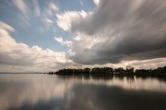 一个湖的长的曝光视图有运动的白色云彩的完全 免版税库存照片