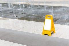 一个湿地板的空白的黄色道路危险标志戒备在喷泉deco 免版税库存图片