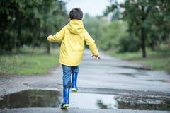 一个湿孩子在水坑跳 在街道上的乐趣 磨炼在夏天 库存图片