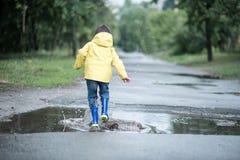 一个湿孩子在水坑跳 在街道上的乐趣 磨炼在夏天 免版税库存照片