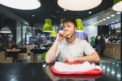 一个滑稽的人在餐馆吃一个开胃汉堡并且看照相机 快餐午餐 库存照片