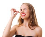 一个滑稽的女孩是鬼脸,并且叮咬用一个酸枣加糖丝带 背景查出的白色 库存图片