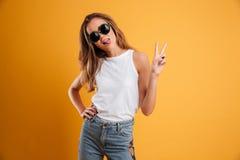 一个滑稽的女孩的画象显示和平姿态的太阳镜的 免版税库存照片