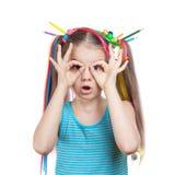 一个滑稽的女孩的画象有五颜六色的子线的在她的头发 女孩在她的眼睛附近握她的手并且看起来惊奇 库存图片