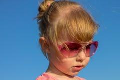 一个滑稽的孩子的画象使用在夏天公园的玻璃的 图库摄影
