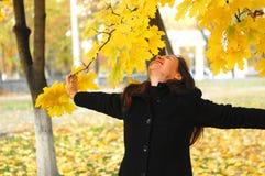 一个滑稽的年轻可爱的女孩有乐趣和无所事事在秋天公园 快乐的情感,秋天心情 免版税库存照片