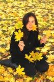 一个滑稽的年轻可爱的女孩有乐趣和无所事事在秋天公园 快乐的情感,秋天心情 免版税库存图片