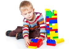 一个滑稽的男孩使用与lego 库存图片