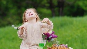 一个滑稽的脏污女孩坐一张桌在庭院里并且吃一个甜蛋糕用她的手,巧克力踪影保持  影视素材