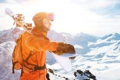 一个滑雪者的画象桔子的整体与在他的后面的一个在他的肩膀的背包和滑雪在盔甲在a站立 免版税库存照片