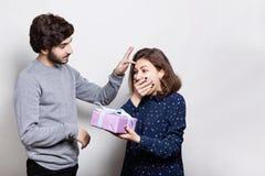 一个激动的浅黑肤色的男人在她的手上的拿着一个礼物惊奇接受它 给礼物的一个仔细的行家他的girlfr 免版税库存图片