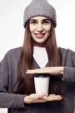 一个灰色帽子的年轻俏丽的妇女拿着纸咖啡杯 布局的外带的包裹 免版税库存照片
