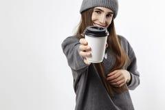 一个灰色成套装备展示的年轻俏丽的妇女从纸杯的一份咖啡 布局的外带的包裹 在杯子的重点 免版税库存图片