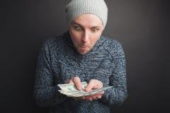 一个灰色盖帽和胡子的一个年轻人,拿着堆金钱和凝视在它在黑背景 自由职业者敬佩它它 免版税库存照片