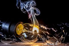 一个灼烧的电灯泡的令人惊讶的爆炸与裂片和烟的 免版税图库摄影