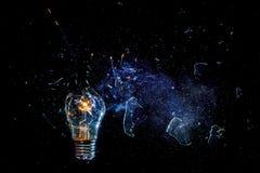 一个灼烧的电灯泡的令人惊讶的爆炸与裂片和烟的 库存图片