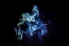 一个灼烧的电灯泡的令人惊讶的爆炸与裂片和烟的 图库摄影