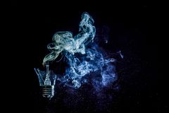 一个灼烧的电灯泡的令人惊讶的爆炸与裂片和烟的 库存照片