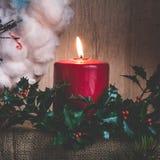 一个灼烧的蜡烛和霍莉分支以圣诞节为背景缠绕 库存照片