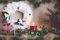 一个灼烧的蜡烛和霍莉分支以圣诞节装饰为背景 库存照片